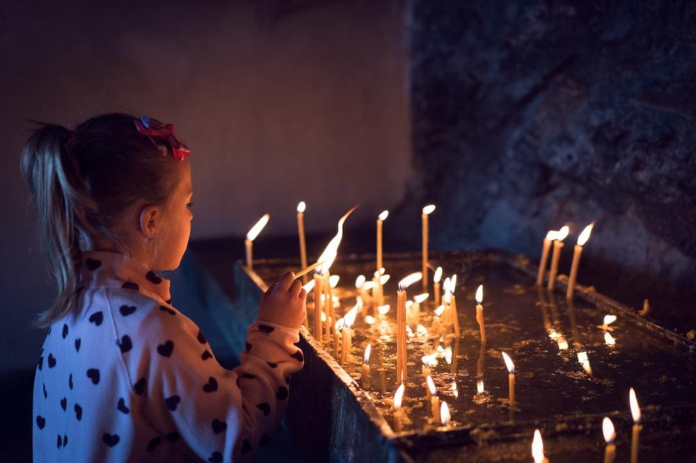 small child lighting memorial candles symbolic of fentanyl deaths